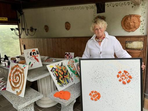 Giovanna Pasello mostra una delle sue opere che saranno esposte a Porto Ceresio da sabato al 9 agosto