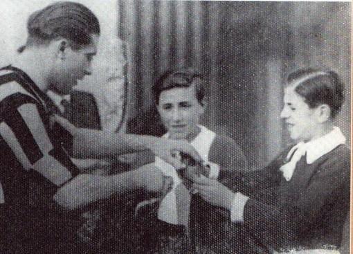 Un giovanissimo Franco Ossola con la maglia della Varese Sportiva durante lo scambio di omaggi floreali all'Arena di Milano con il mito Giuseppe Meazza