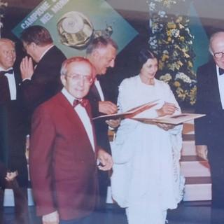 Lucio Piccoli, in giacca bordeaux, con Carla Fracci