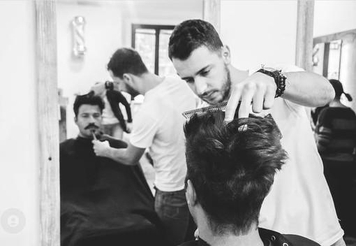 Roberto Gerosa (in una foto al lavoro pre-pandemia) allarga la sua attività in tempo di Covid: apre una nuova barberia a Castellanza